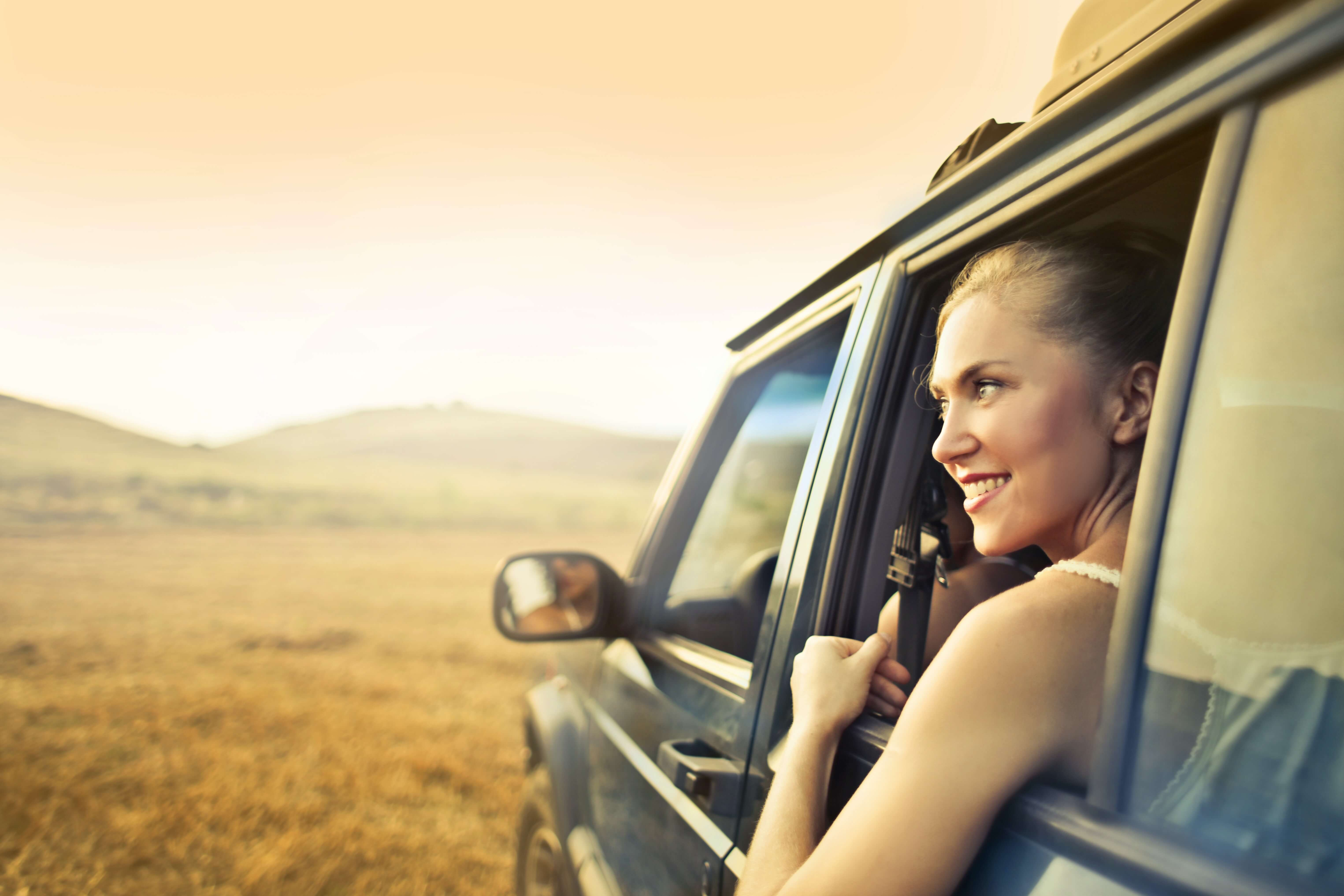 cheerful-glow-getter-woman-in-car-enjoying-sunset